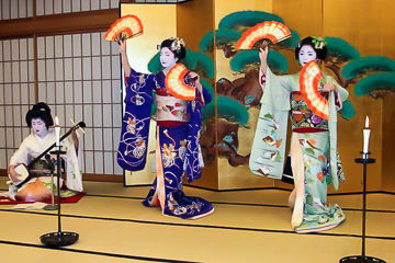 Maiko dancing while a geisha plays music